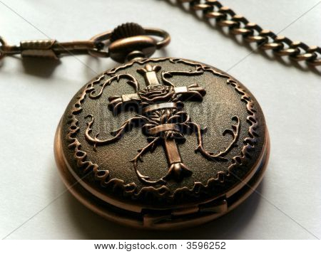 Close-up of a closed hunter-style copper pocket watch engraved with a cross.