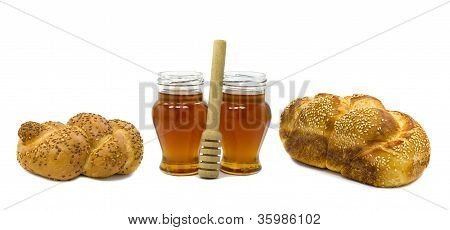 Two  challahs and two jars of  honey isolated on white background