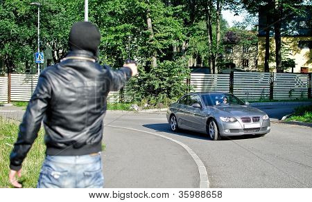 Man In Mask Pointing Gun Toward Car. Robbery Concept
