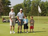stock photo of happy family  - Two Generations of Family Playing Golf Together - JPG
