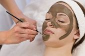 stock photo of mud pack  - A beautiful young brunette woman having a chocolate face mask applied by a beautician - JPG