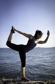 picture of natarajasana  - Young women in upright yoga pose with water in background in King Dancer - JPG