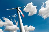 foto of dynamo  - low angle view of a wind turbine against a blue sky with white clouds - JPG