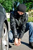 foto of revenge  - Man in mask punctures a car tyre - JPG