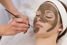 pic of mud pack  - A beautiful young brunette woman having a chocolate face mask applied by a beautician - JPG