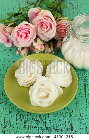 Sugar roses and natural roses, glass jar with sugar,  on color background
