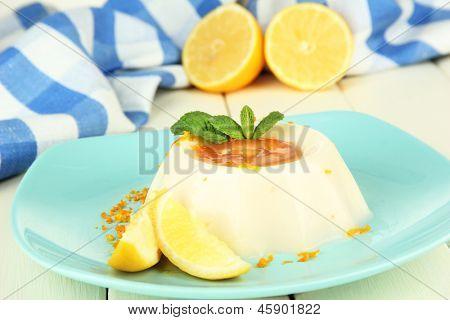 Lemon Panna Cotta with orange zest and caramel sauce, on color wooden background