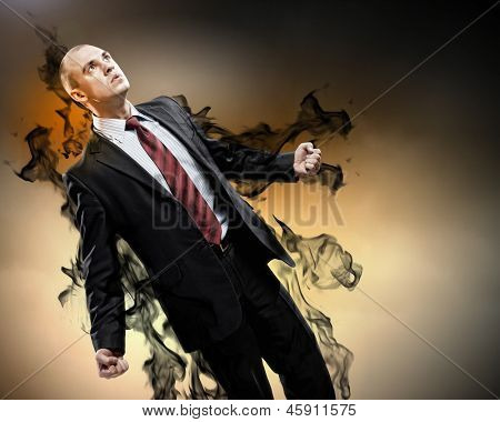 Image of young businessman in anger standing in black smoke