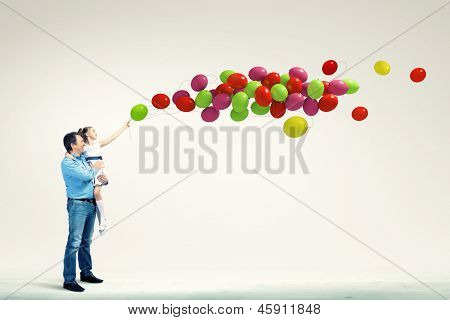 Image of happy father holding on hands daughter and balloons
