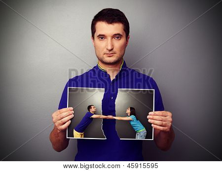 serious young man holding the lacerated photo of young couple in parting