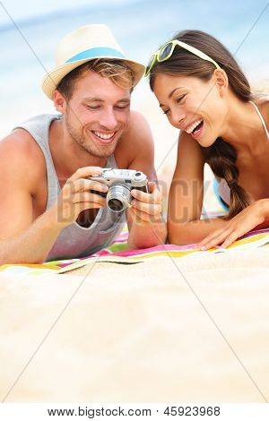 Happy couple fun on beach laughing together looking at summer vacation travel photo pictures on retro vintage camera. Joyful interracial trendy modern hipster couple, Asian woman, Caucasian man.