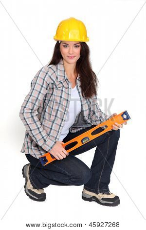 Woman kneeling with spirit-level