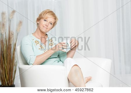 Woman having coffee while relaxing at home