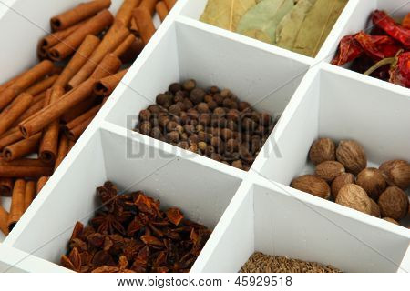 Assortment of aroma spices in white wooden box close up