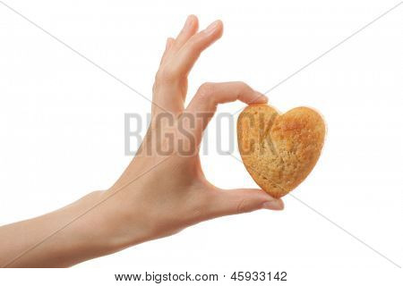 Hand holding heartshape cake, isolated on white