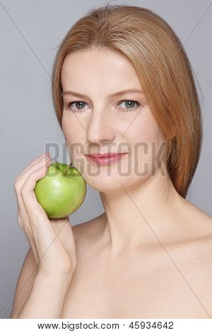 Portrait of beautiful healthy happy mature woman with clear skin and green apple in her hands