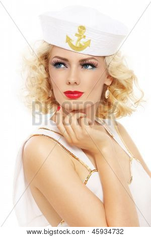 Young beautiful sexy girl with blond curly hair and stylish make-up dressed as sailor, over white background