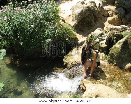 Young Woman Sitting At The Stream
