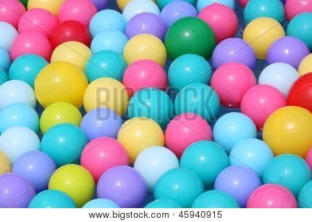 Colourful plastic balls floating on water