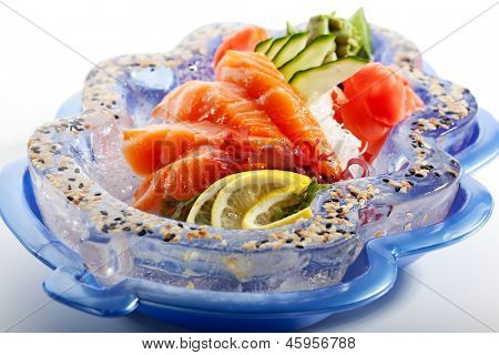 Salmon Sashimi - Sliced Raw Salmon on Daikon (White Radish) with Seaweed, Lime and Cucumber. Garnished on Ice Plate