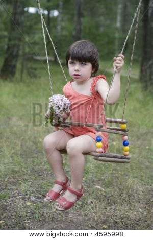 Litle Cute Girl Sitting On Swing.