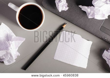 business creativity concept. Laptop, sheets of paper and crumpled wads on table.