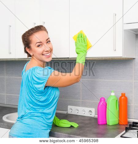 smiling cute woman cleans the kitchen at her home