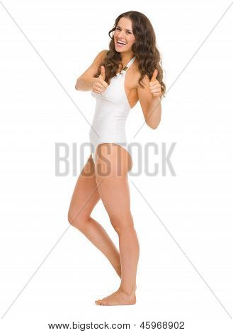 Full Length Portrait Of Smiling Young Woman In Swimsuit Showing Thumbs Up