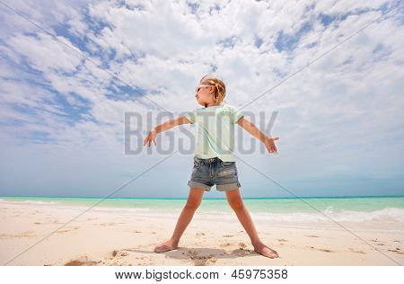 Portrait of cute little girl at tropical beach made with wide angle lens