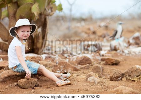 Little girl on Galapagos North Seymour island with a blue footed booby on background