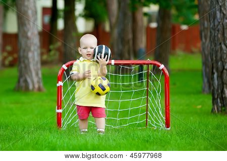 Small Caucasian Boy Plays Football In Park