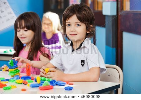 Portrait of cute little boy with blocks while friends playing in background