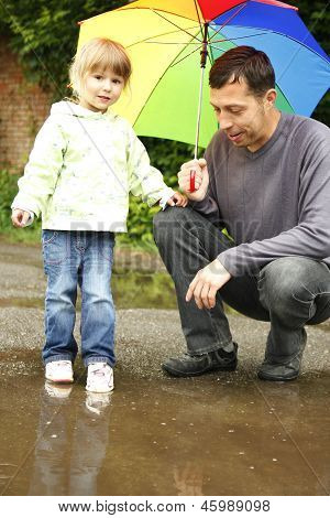 Girl With An Umbrella In The Rain With His Father
