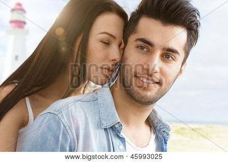 Summer portrait of young attractive loving couple on the beach.
