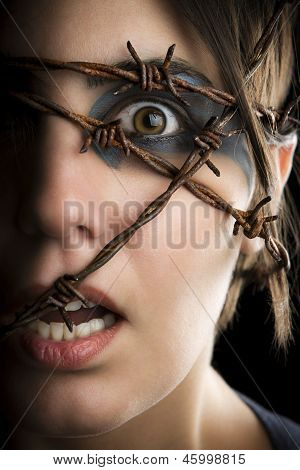 Terrified woman with barbed wire around the head.