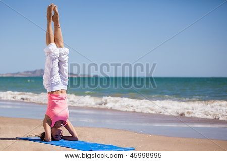 Standing on her head at the beach