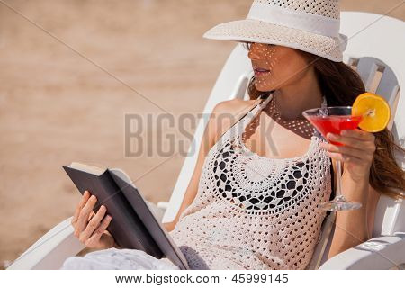 Drinking and reading at the beach