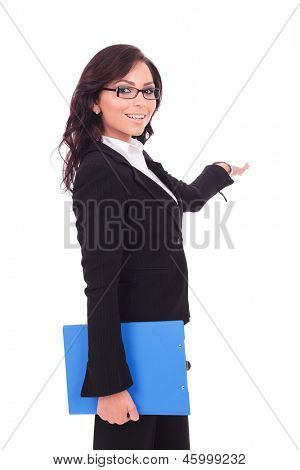 young business woman presents something in the back while holding a clipboard in her other hand and smiling to the camera. on white background