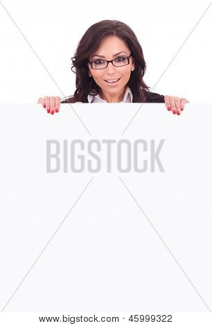 young business woman standing behind an empty board and smiling to the camera. on white background