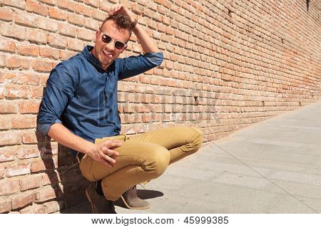casual young man goofing around while sitting crouched by a brick wall, scratching his head and pulling his tongue out, while looking at the camera