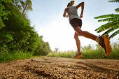 stock photo of cross hill  - Young lady running on a rural road - JPG