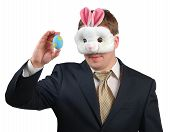 picture of peter cottontail  - Young man wearing suit with Easter Bunny mask looking at an Easter egg which he is holding in front of his face - JPG
