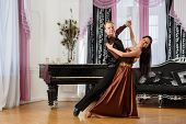 stock photo of waltzing  - a dancing young couple in the room  - JPG