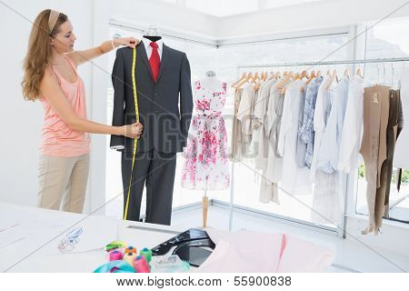 Side view of a female fashion designer measuring suit on dummy at the studio