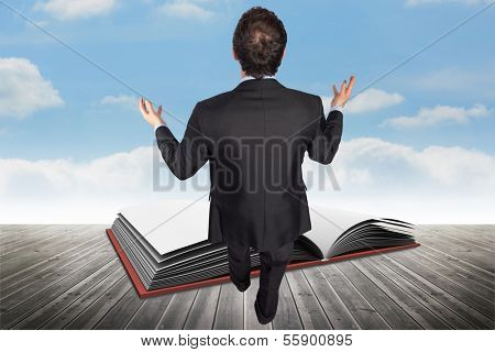 Gesturing businessman against open book against sky