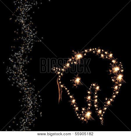Christmas sparklers in shape of horse on black background