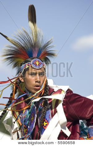 Native American man with colorful head piece.