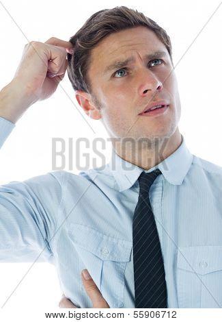 Thinking businessman scratching head on white background