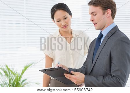 Portrait of two business colleagues standing with clipboard at office
