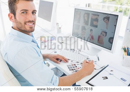 Side view portrait of a male photo editor working on computer in a bright office